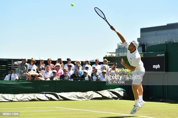 US player Denis Kudla serves to France's Lucas Pouille during their men's singles first round match on the first day of the 2018 Wimbledon...