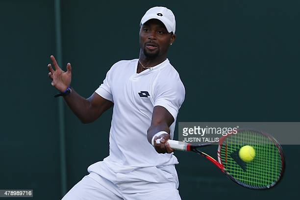US player Donald Young returns against Cyprus's Marcos Baghdatis during their men's singles first round match on day one of the 2015 Wimbledon...