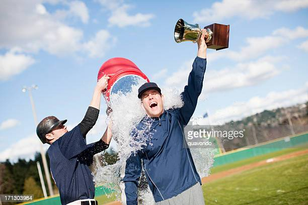 Player dumping Gatorade on coach holding a trophy