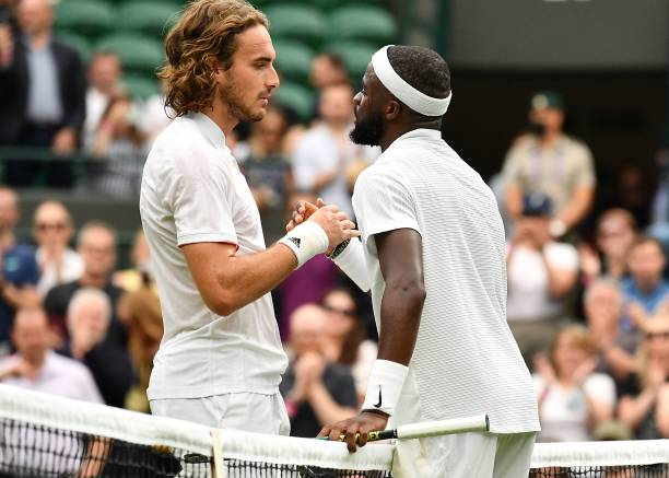 Player Frances Tiafoe greets Greece's Stefanos Tsitsipas after winning their men's singles first round match on the first day of the 2021 Wimbledon...