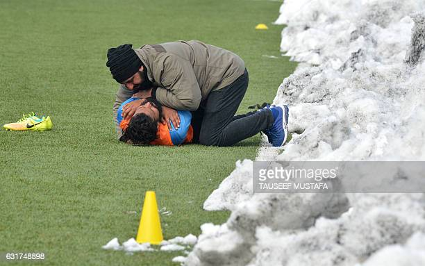 A player from Real Kashmir Football Club stretches during a practice match at Srinagar football stadium on January 15 2017 Real Kashmir Football Club...