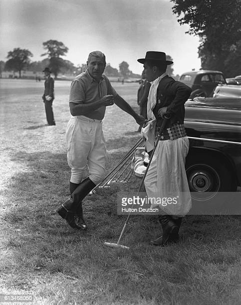 A player from the Argentine polo team La Espandana wearing a gaucho costume chats to an attendant during the Festival Cup event at which they lost to...