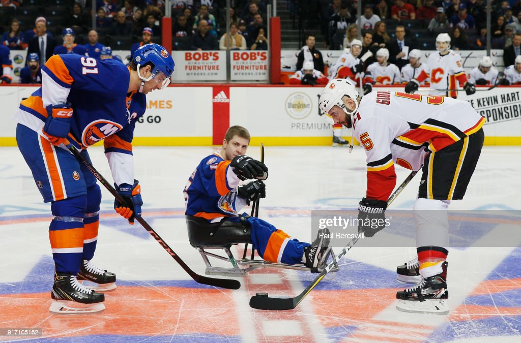 A player from the Long Island RoughRiders sled hockey team takes part in the ceremonial puck drop with John Tavares #91 of the New York Islanders and Mark Giordano #5 of the Calgary Flames prior to a game at Barclays Center on February 11, 2018 in the Brooklyn borough of New York City.