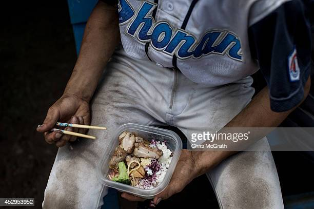 A player from the Shonan Boys eats lunch in the dugout during a practice game between the Shonan Boys and the Yokohama Minami on July 30 2014 in...