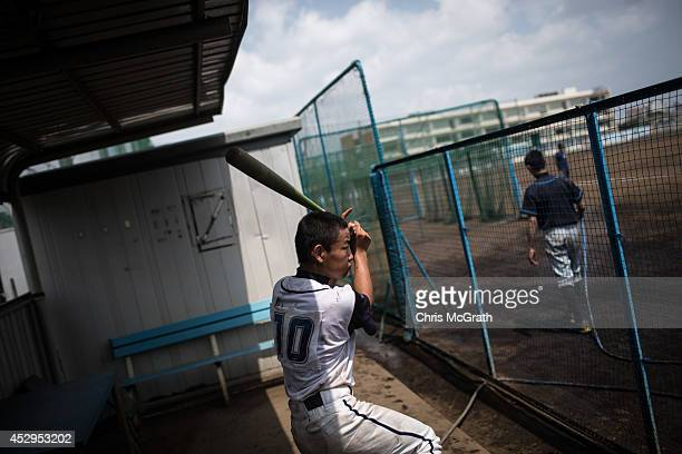 A player from the Shonan Boys practices his swing in the dugout during a practice game between the Shonan Boys and the Yokohama Minami on July 30...