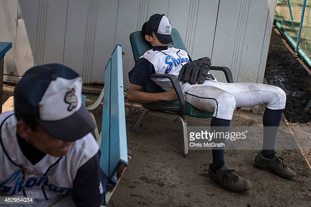 A player from the Shonan Boys rests in the dugout between games during a practice game between the Shonan Boys and the Yokohama Minami on July 30...