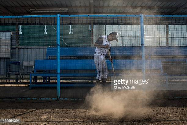 A player from the Shonan Boys sweeps dirt from the dugout after the final practice game between the Shonan Boys and the Yokohama Minami on July 30...