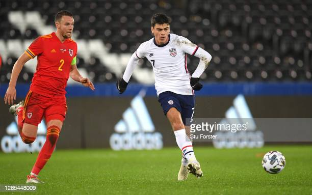 Player Giovanni Reyna beats Chris Gunter to the ball during the international friendly match between Wales and the USA at Liberty Stadium on November...