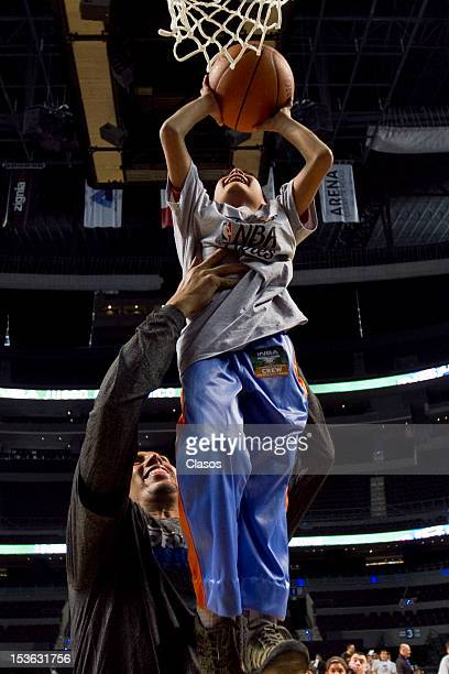 Player Gustavo Ayon plays with a kid during a training session of New Orleans Hornets and Orlando Magic with disabled people at Arena on October 06...