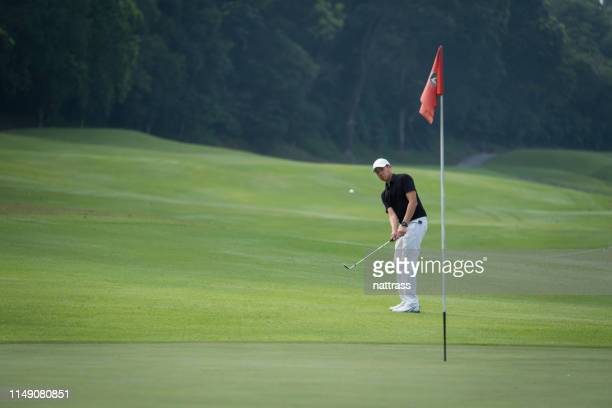 player hitting ball on golf course - golf flag stock photos and pictures