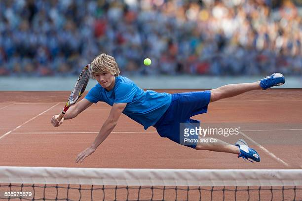 player hitting the ball on clay court tennis