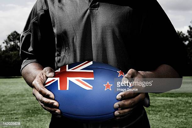 player holding rugby ball with new zealand flag - new zealand rugby stock photos and pictures