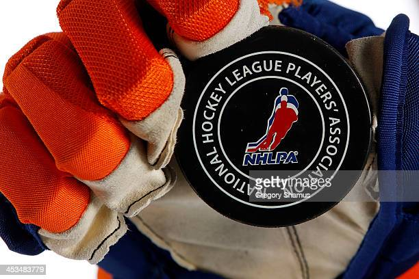 A player holds a hockey puck showing a detailed view during the NHLPA The Players Collection portraits at The Westin Harbour Castle hotel on August...