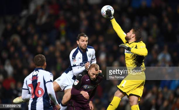 WBA player Jay Rodriguez challenges Swansea goalkeeper Kristoffer Nordfeldt during the Sky Bet Championship match between West Bromwich Albion and...