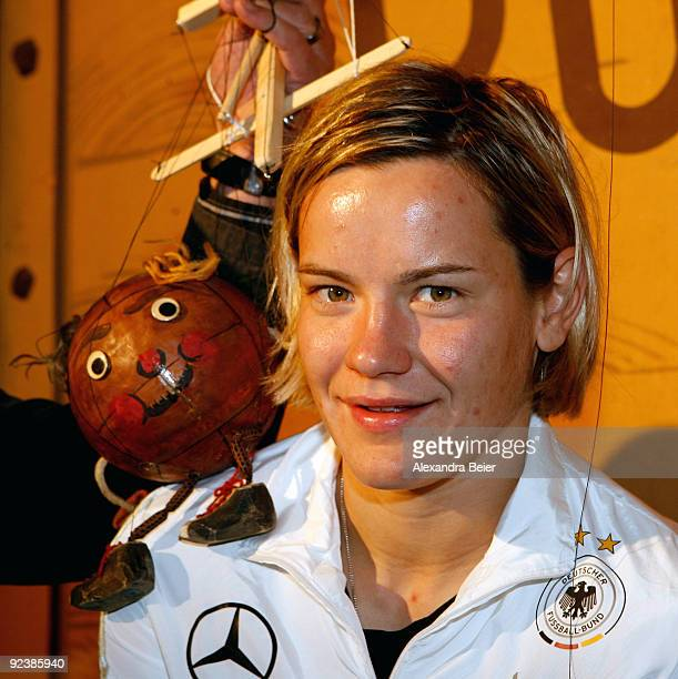Player Jennifer Zietz of the women's German national soccer team smiles as she poses with a soccer ball marionette during her visit at the...