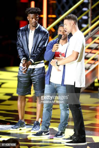 NBA player Jimmy Butler host Russell Wilson and NBA player Klay Thompson participates in a competition onstage during Nickelodeon Kids' Choice Sports...