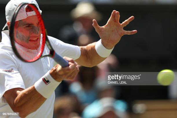 US player John Isner returns against South Africa's Kevin Anderson during their men's singles semifinal match on the eleventh day of the 2018...