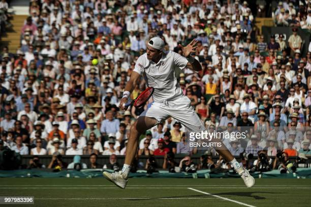 US player John Isner returns against South Africa's Kevin Anderson during the final set tiebreak of their men's singles semifinal match on the...