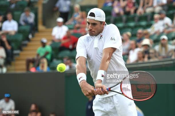 US player John Isner returns to Moldova's Radu Albot in their men's singles third round match on the fifth day of the 2018 Wimbledon Championships at...