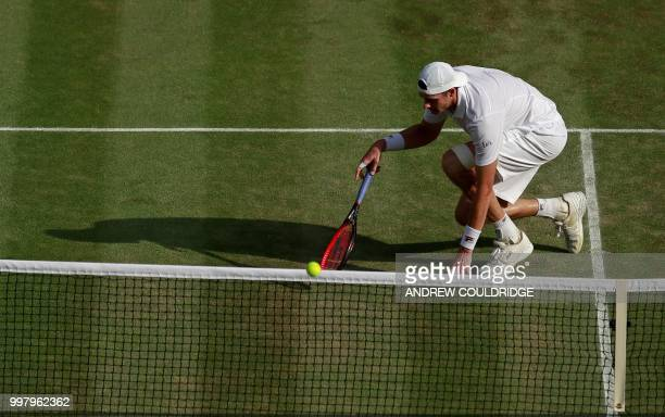 Player John Isner slips as he attempts to return against South Africa's Kevin Anderson during the final set tie-break of their men's singles...