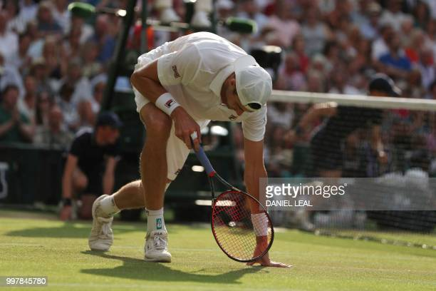 TOPSHOT US player John Isner slips on the grass as he attempts to return against South Africa's Kevin Anderson during the final set tiebreak of their...
