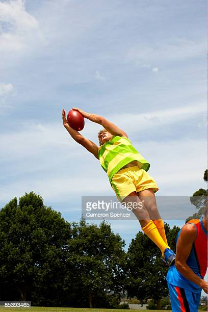player jumps to catch australian football - australian rules football stock-fotos und bilder