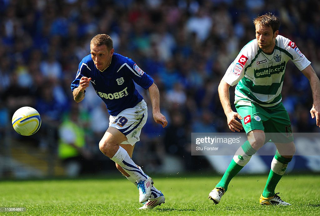 QPR player Kaspars Gorkss (r) battles for the ball with Cardiff player Craig Bellamy during the npower Championship game between Cardiff City and Queens Park Rangers at Cardiff City Stadium on April 23, 2011 in Cardiff, Wales.