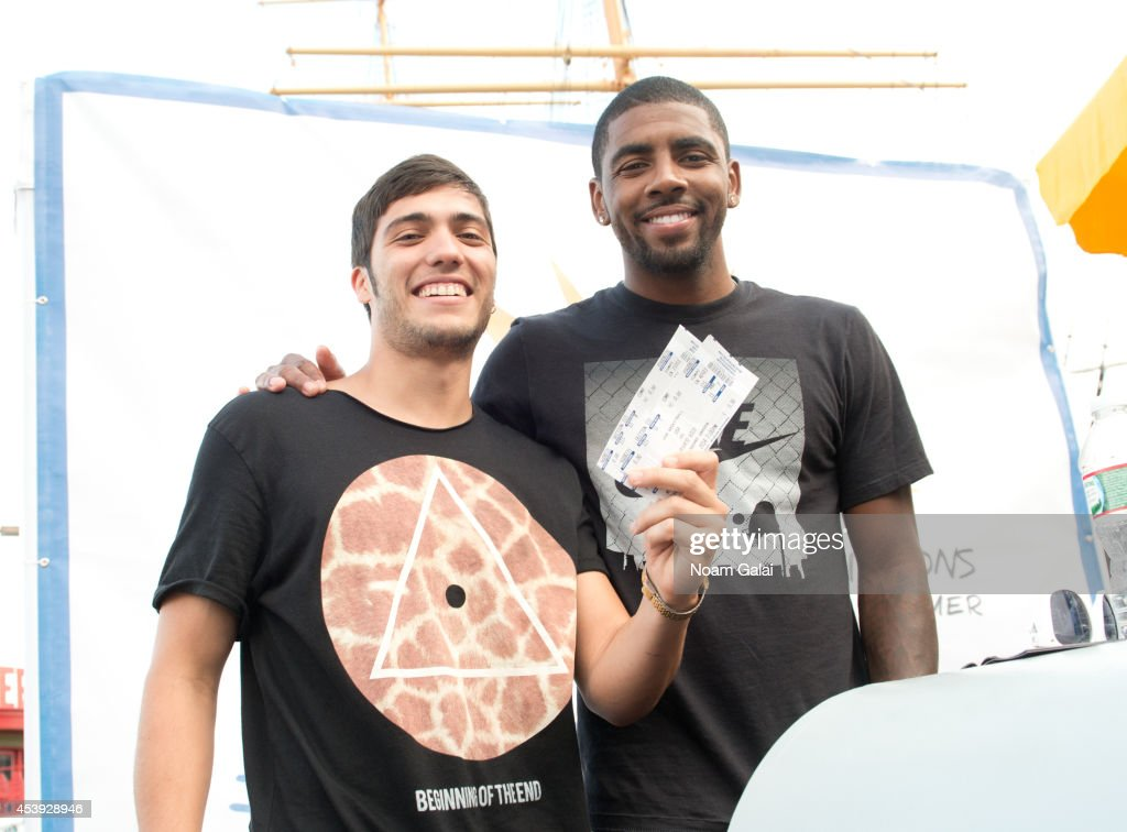 NBA player Kyrie Irving (R) gives a fan tickets for the upcoming USA Basketball team game at The Summer Of Jeep at South Street Seaport on August 21, 2014 in New York City.