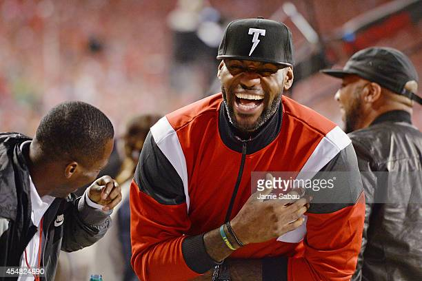 NBA player LeBron James enjoys a laugh with friends on the sideline at Ohio Stadium during the game between the Ohio State Buckeyes and the Virginia...