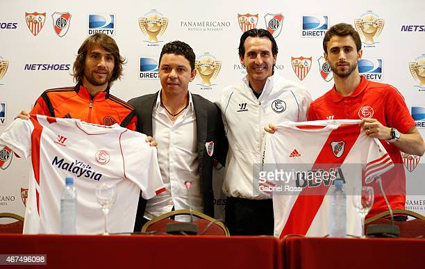 Player Leonardo Ponzio and head coach Marcelo Gallardo of River Plate head coach Unai Emery and player Nicolas Pareja of Sevilla FC after the...