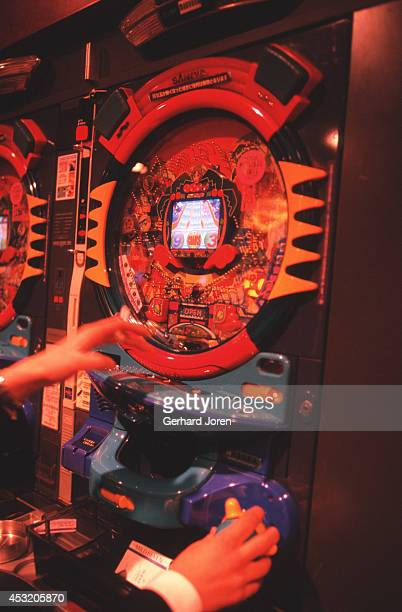 A player manipulates a pachinko machine at the Maruhan Pachinko Tower in Tokyo's fashionable Shibuya district Over 500 machines service over 5000...