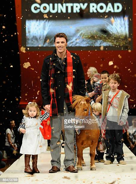 AFL player Matthew Lloyd and models showcase designs on the catwalk by Country Road during the Fashion Collections Mini Me collection show as part of...