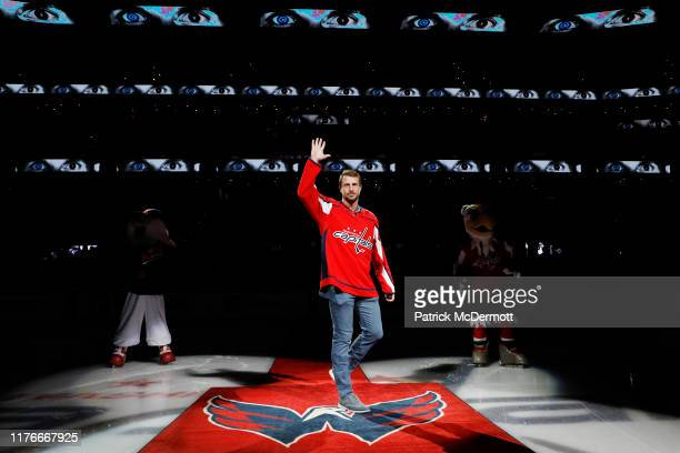 MLB player Max Scherzer of the Washington Nationals waves to the crowd before taking part in a ceremonial puck drop before a game between the New...