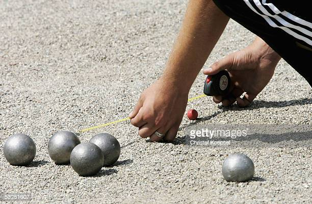 A player measures the distance from a boule to the jack during the Petanque discipline of the World Games 2005 on July 18 2005 in Duisburg Germany