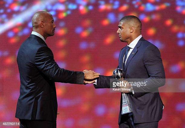 NFL player Michael Sam accepts the Arthur Ashe Courage Award from actor Dwayne The Rock Johnson onstage during the 2014 ESPYS at Nokia Theatre LA...