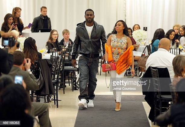Player Michael Vick and Kijafa Vick walk the runway at the Saks Fifth Avenue And Off The Field Players' Wives Association Charitable Fashion Show on...