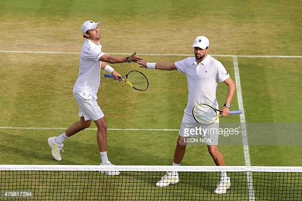 US player Mike Bryan and his partner Bob Bryan touch hands between points against India's Rohan Bopanna and Romania's Florin Mergea during their...