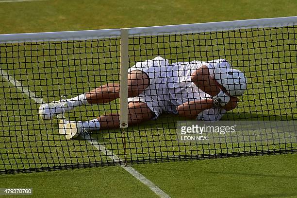 US player Mike Bryan lies on the court in the front of the net after he was hit by the ball from the service of his partner Bob Bryan during their...