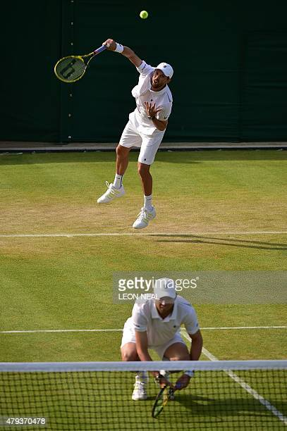 US player Mike Bryan serves over the head of his partner US player Bob Bryan as they play against US player Sam Querrey and US player Steve Johnson...