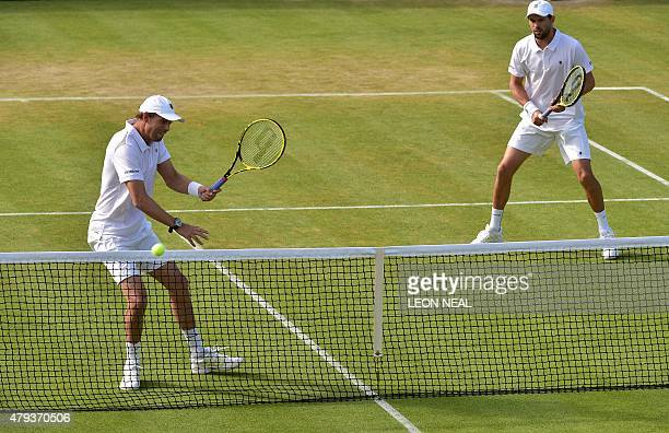 US player Mike Bryan stands ready as his partner US player Bob Bryan returns at the net against US player Sam Querrey and US player Steve Johnson...