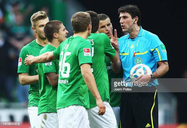 Player of Bremen talk to referee Markus Wingenbach after the Bundesliga match between SV Werder Bremen and FC Augsburg at Weser Stadium on March 24,...