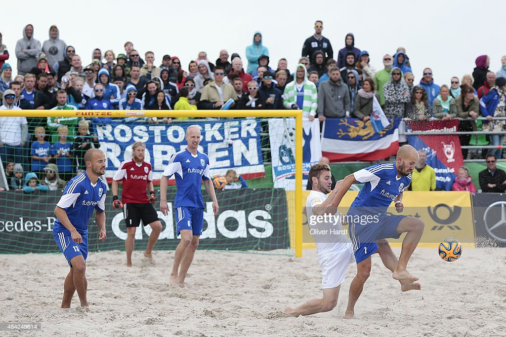 Player of Chemnitz (C) challenges a player of Rostock (R) during the final match between BST Chemnitz and Rostocker Robben on day one of the DFB Beachscoccer Cup at the beach of Warnemunde on August 24, 2014 in Warnemunde, Germany.