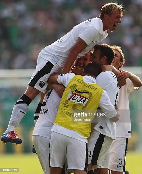 Player of Muenster celebrate after winning the DFB Cup first round match between Preussen Muenster and Werder Bremen at Preussenstadion on August 19,...