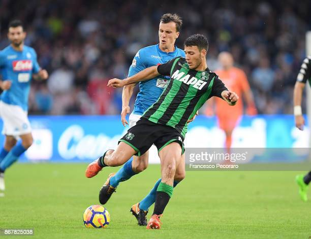 Player of SSC Napoli Vlad Chiriches vies with US Sassuolo player Luca Mazzitelli during the Serie A match between SSC Napoli and US Sassuolo at...