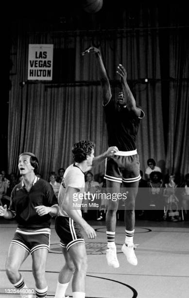 Player of the Denver Nuggets David Thompson shoots over NBA player of the Phoenix Suns Paul Westphal as American singer, composer, actor, writer,...