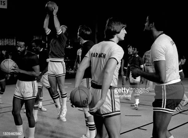 """Player of the New Orleans Jazz """"Pistol"""" Pete Maravich talks with NBA player of the Portland Trail Blazers Maurice Lucas as American singer,..."""