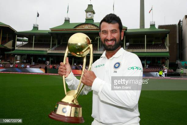 Player of the series Cheteshwar Pujara of India holds up the Border–Gavaskar Trophy as he celebrates India's 21 series win after day five of the...