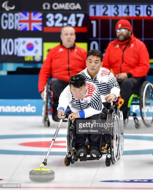 Player of the South Korean team delivers a stone during a round-robin wheelchair curling match against Britain at the Pyeongchang Paralympics in...