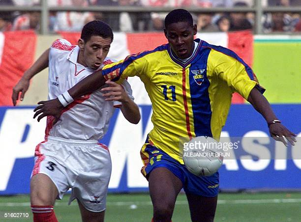 A player on the Peruvian national team Miguel Rebosio chases the ball with Agustin Delgado of the Ecuadorean team in pursuit 02 June 2001 in Liman...