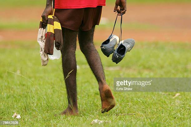 A player on the Tapalinga Super Stars shows up barefoot but carrying his boots for their against the Muluwurri Magpies in a game of Australian Rules...